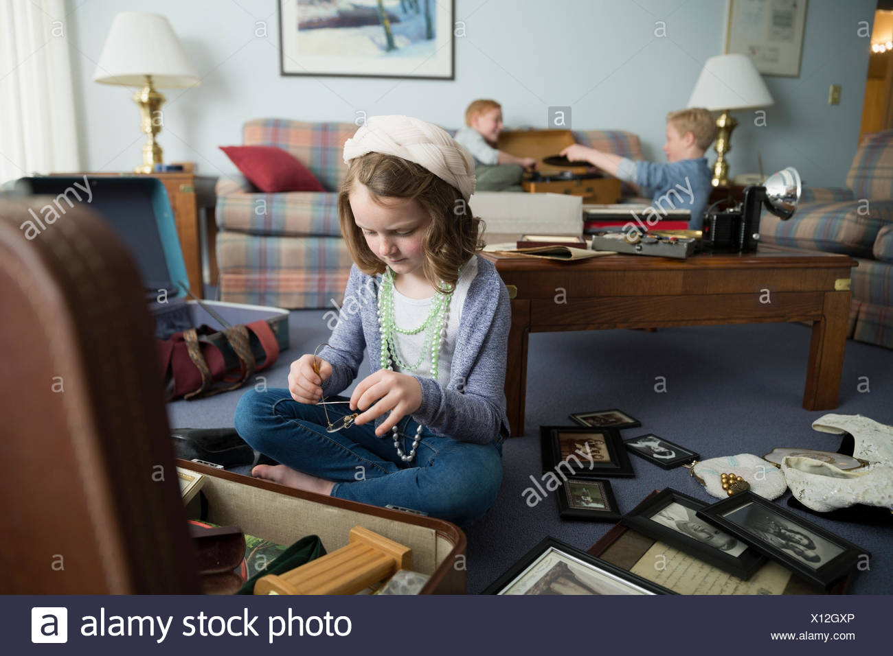 Curious girl going through memorabilia - Stock Image