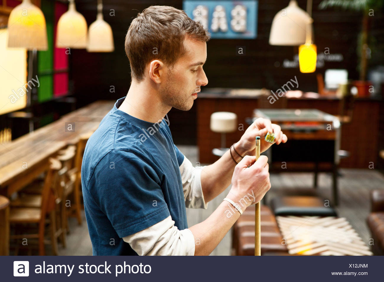 Man playing pool in bar - Stock Image
