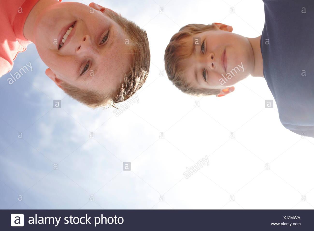 Two boys looking at camera, viewed from below - Stock Image