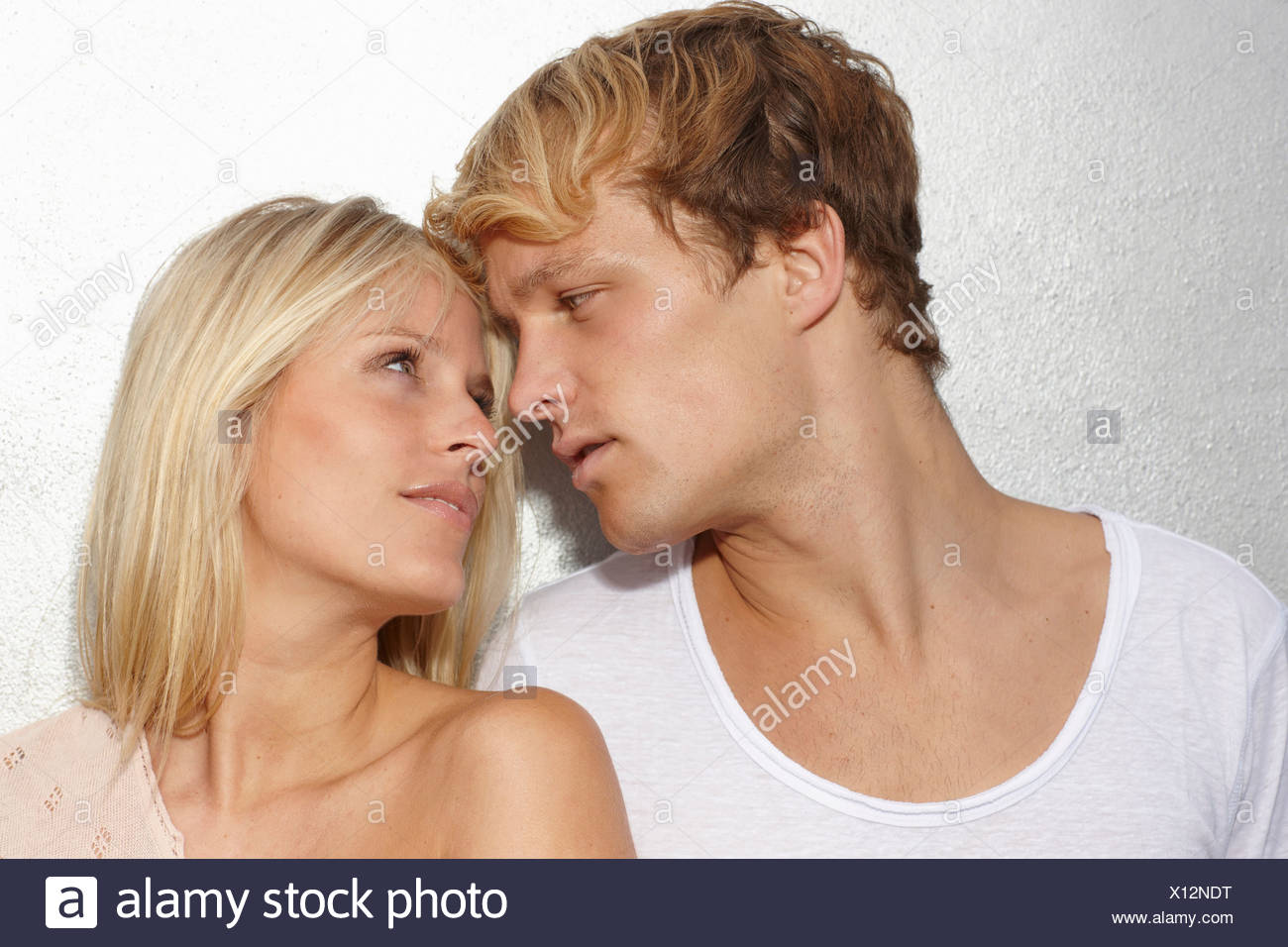 Portrait of young couple looking into each others eyes - Stock Image
