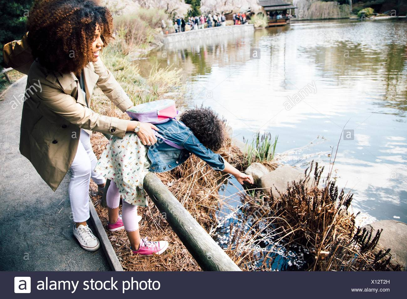 Mother gripping daughter stretching over guard rail to touch plant - Stock Image