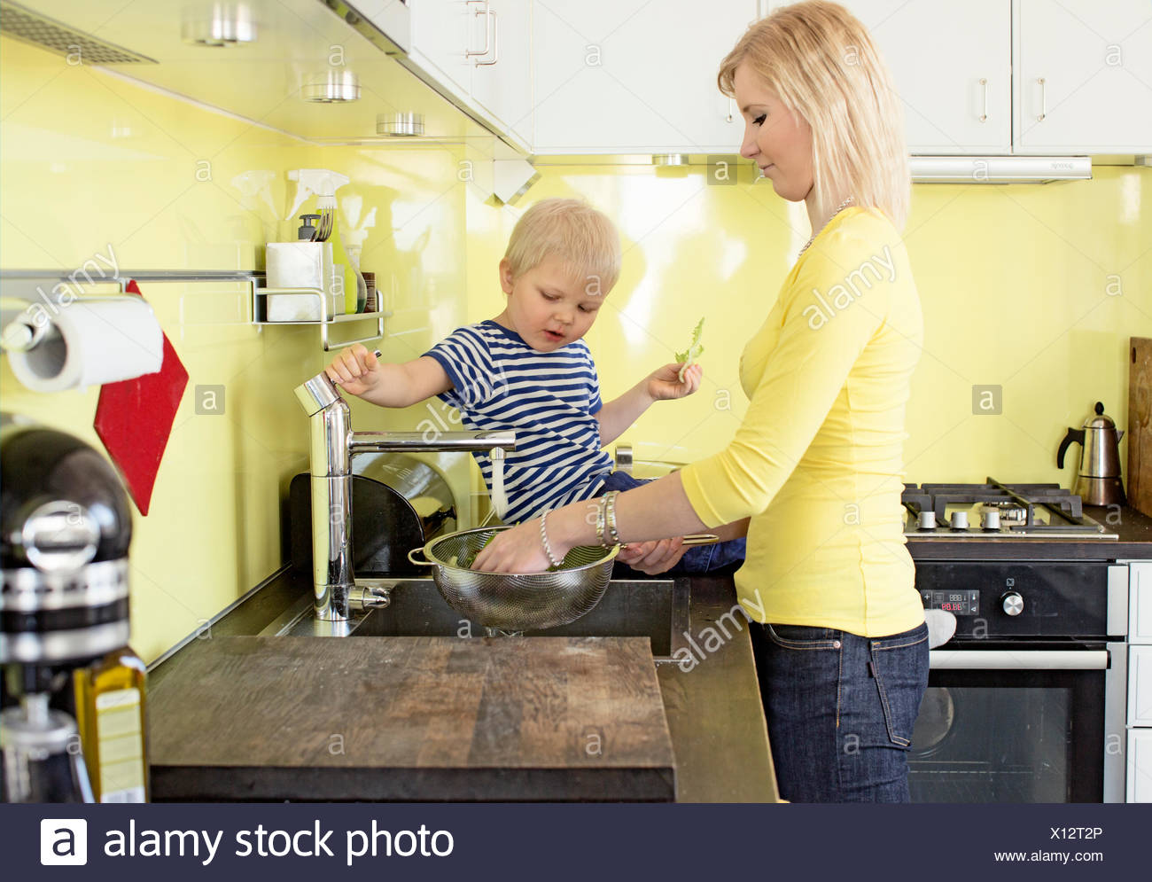 Finland, Helsinki, Kallio, Mother and son in kitchen rinsing vegetables in colander - Stock Image