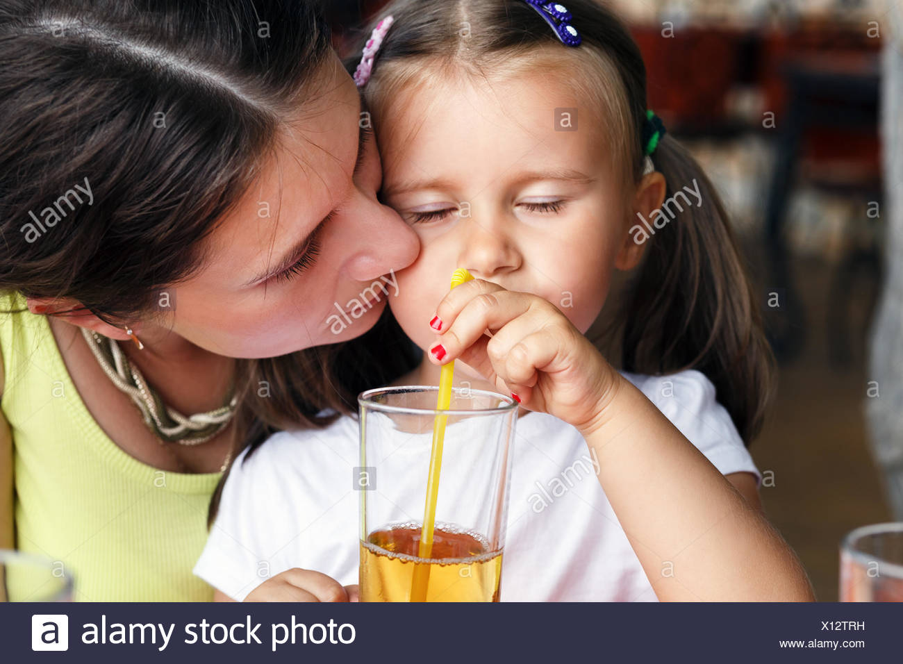 Mom kisses her little daughter - Stock Image