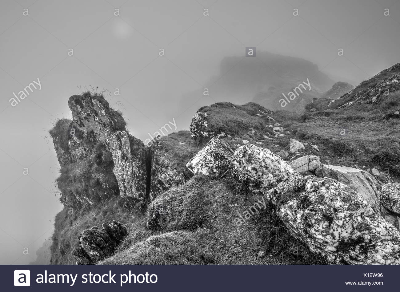 Craggy Mountain Top in Fog with Weak Sun - Stock Image