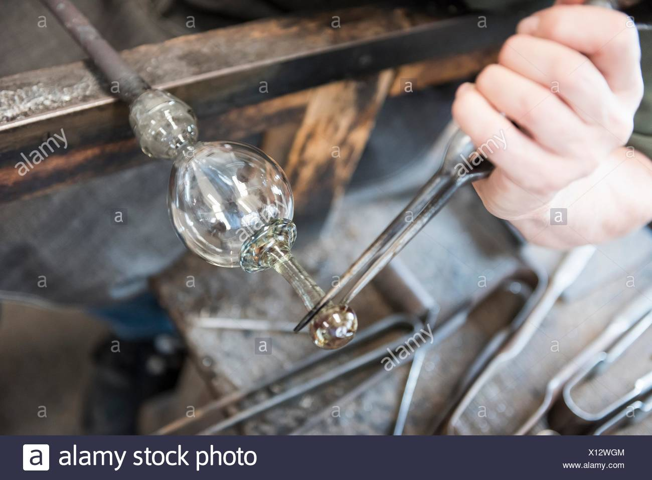 Glassblower forming hot glass object, close up - Stock Image