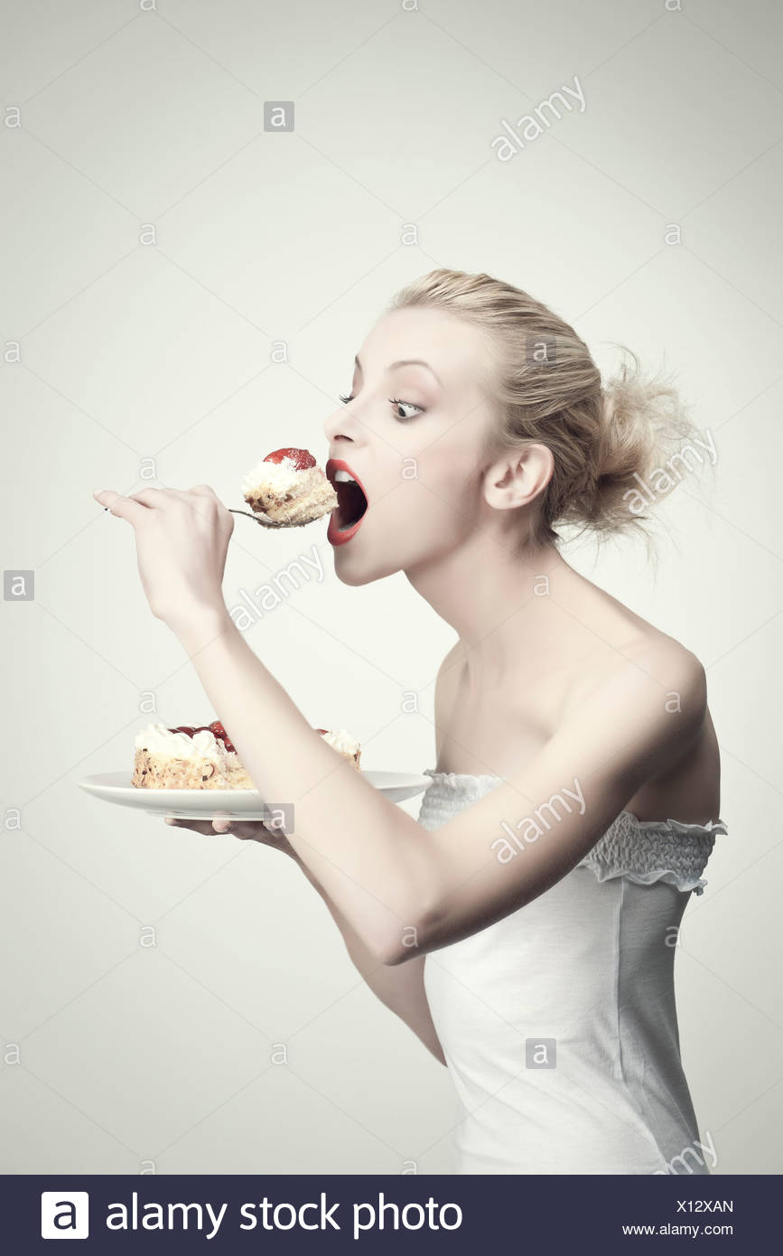 Young woman eating cake, side view, portrait - Stock Image
