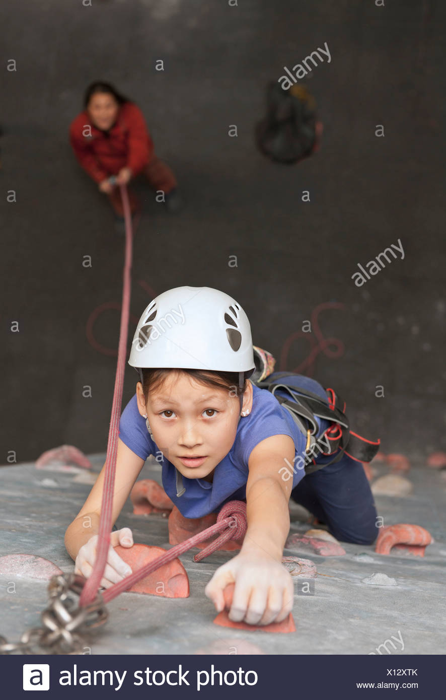 Girl climbing indoor rock wall - Stock Image