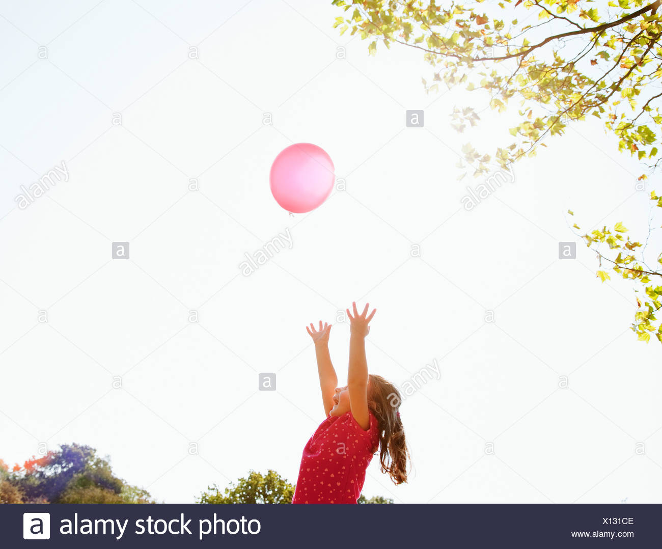 Girl reaching for red balloon in sunny sky - Stock Image