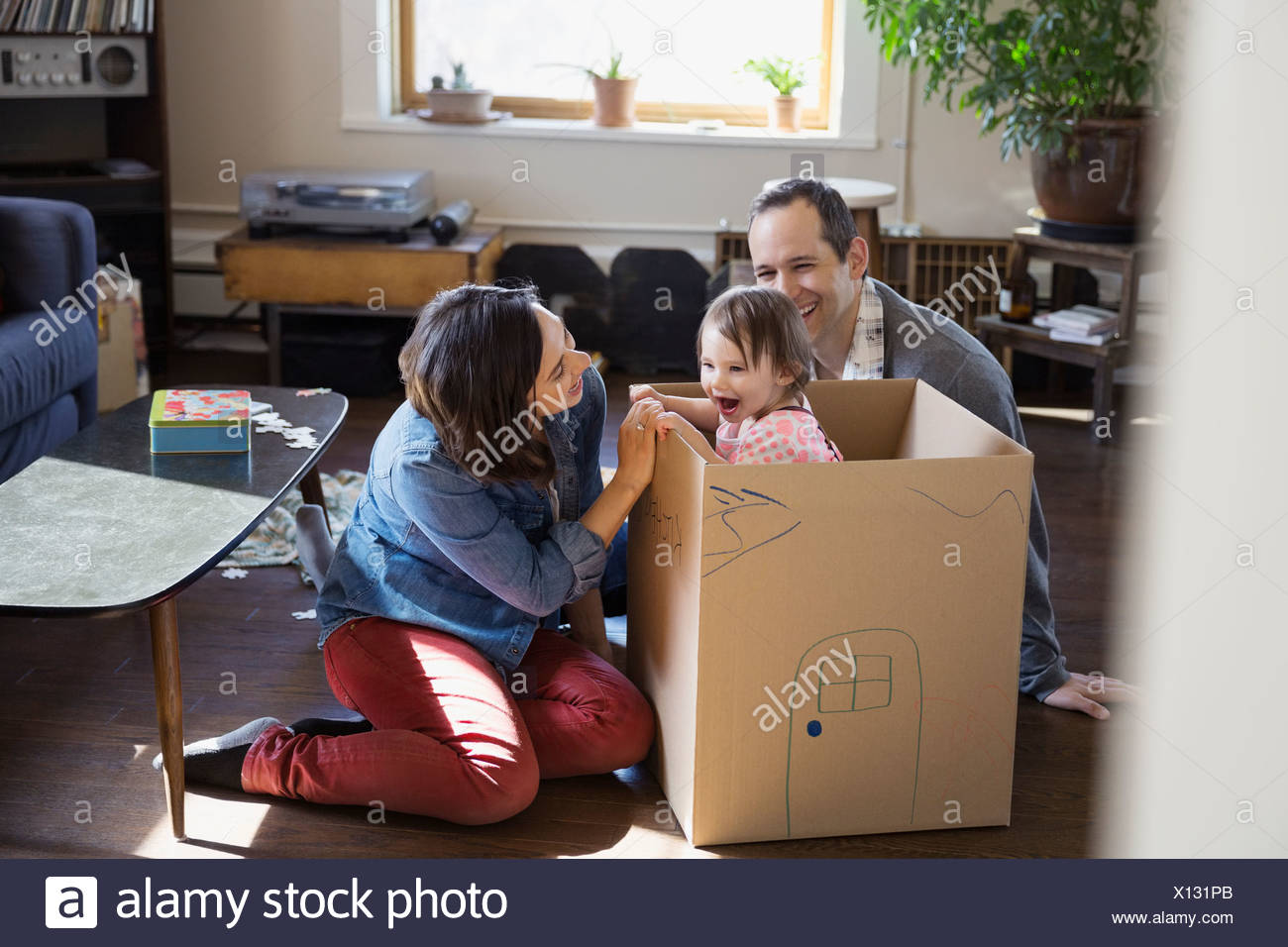 Young family playing in living room - Stock Image