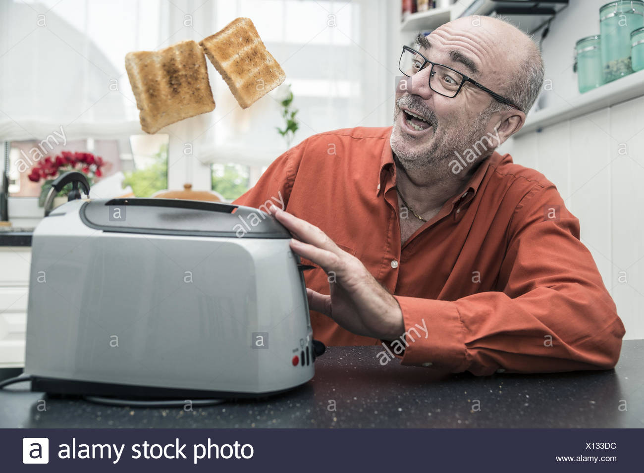 man watches as jump 2 slices of toast from the toa - Stock Image