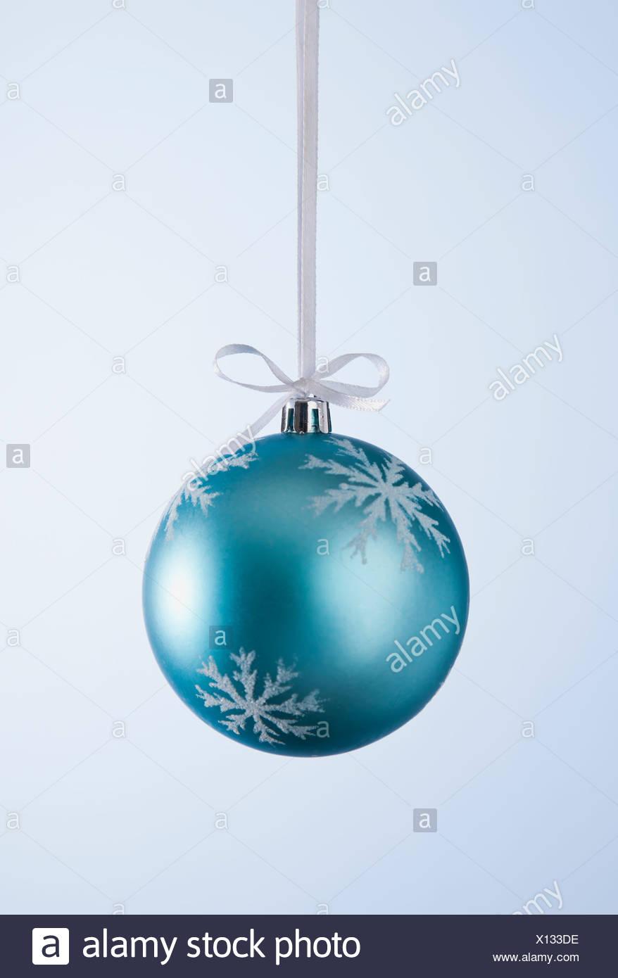 Studio shot of blue Christmas ornament hanging on ribbon - Stock Image