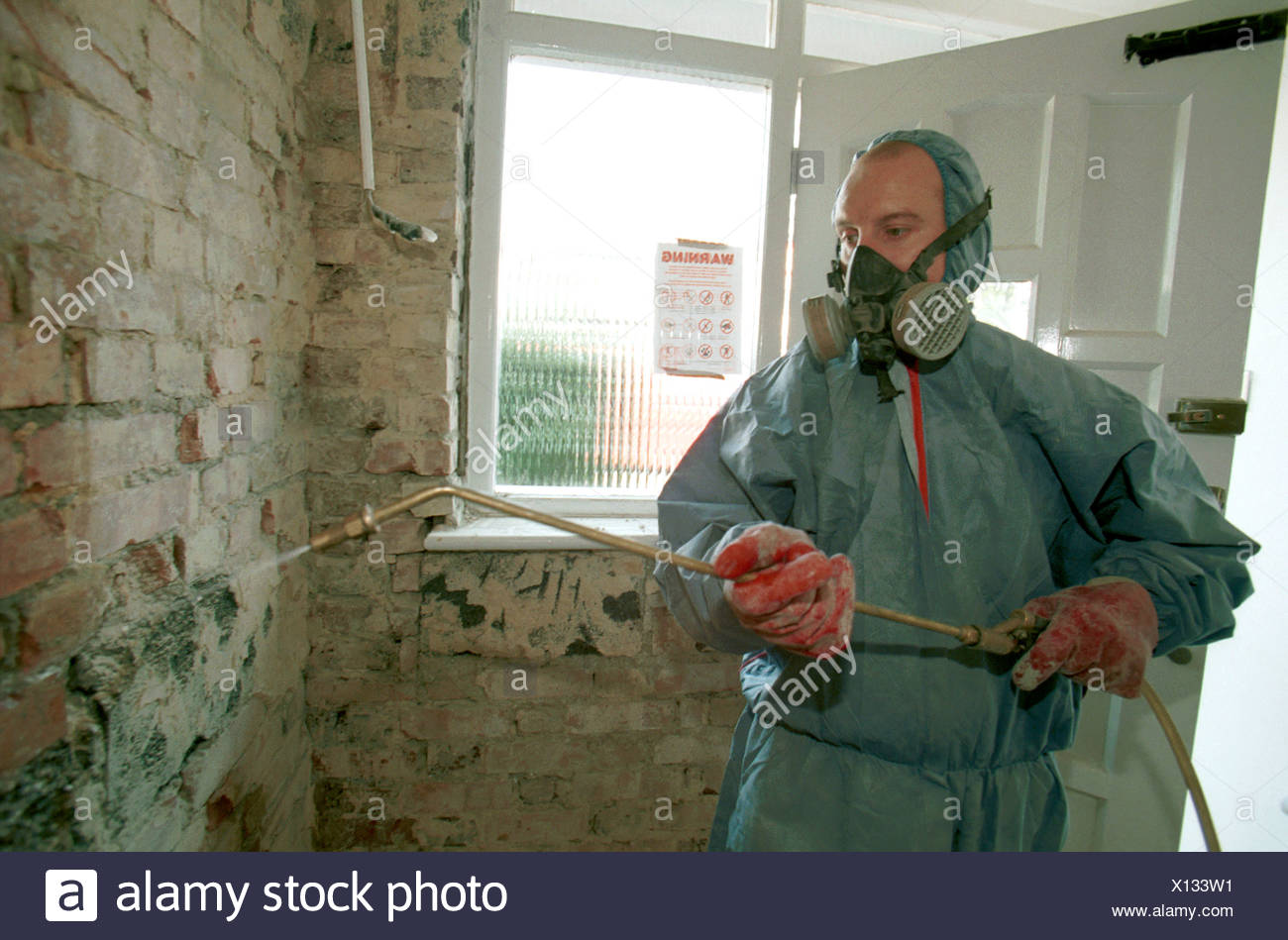 Damp Proofing. Applying chemical treatments with a spray gun. - Stock Image