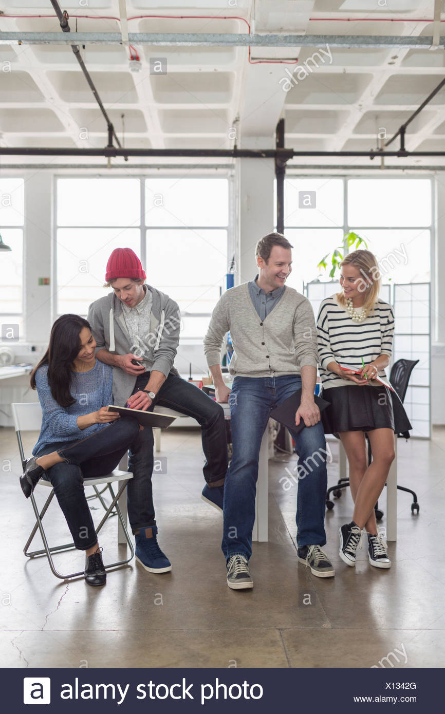 Creative business team sitting together in office - Stock Image