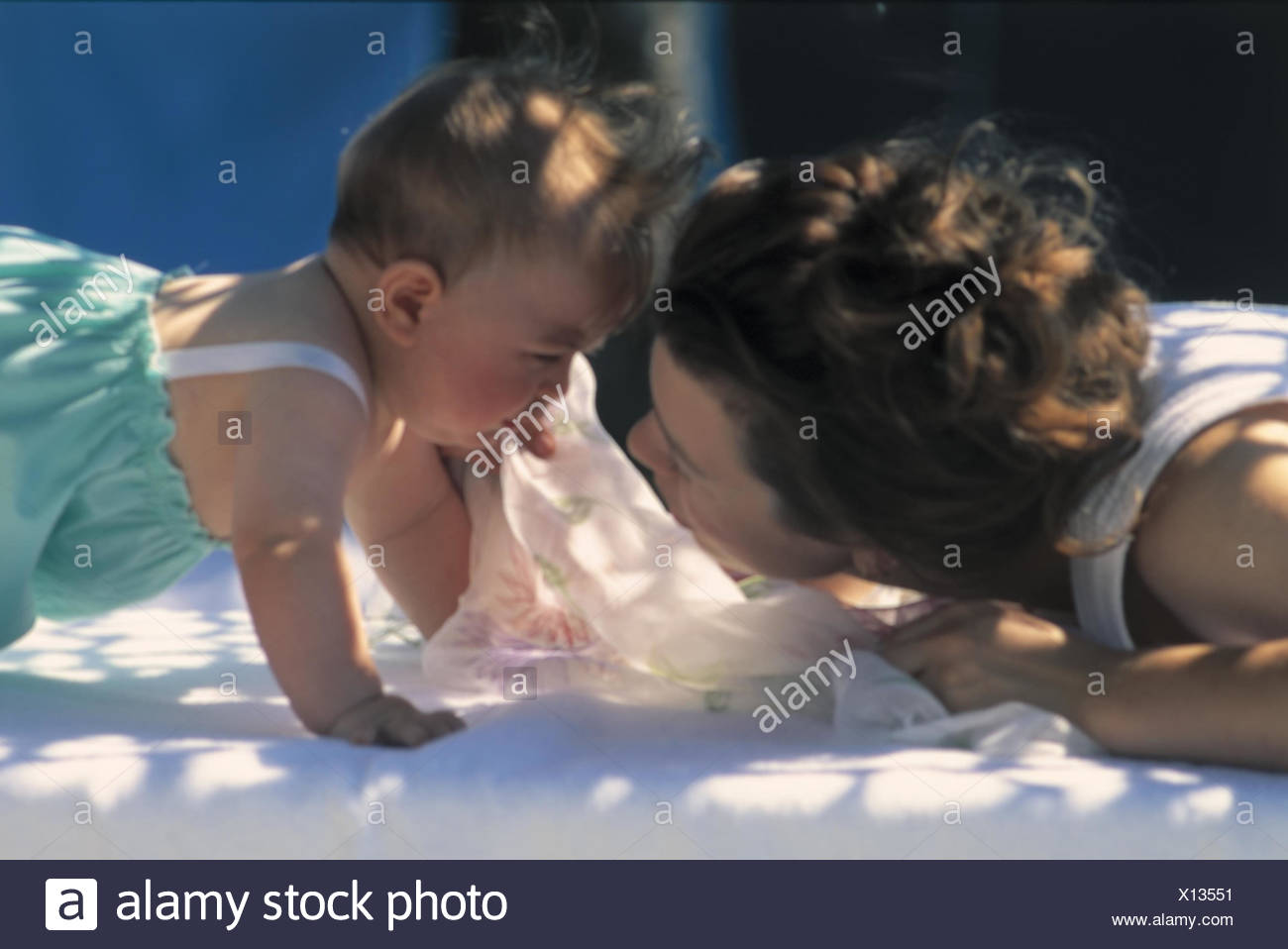 Mother, baby, eye contact, facial play, portrait outside, summer, woman, parent, young, child, cry, tearful, creep, love, affection, affectionately, comfort - Stock Image