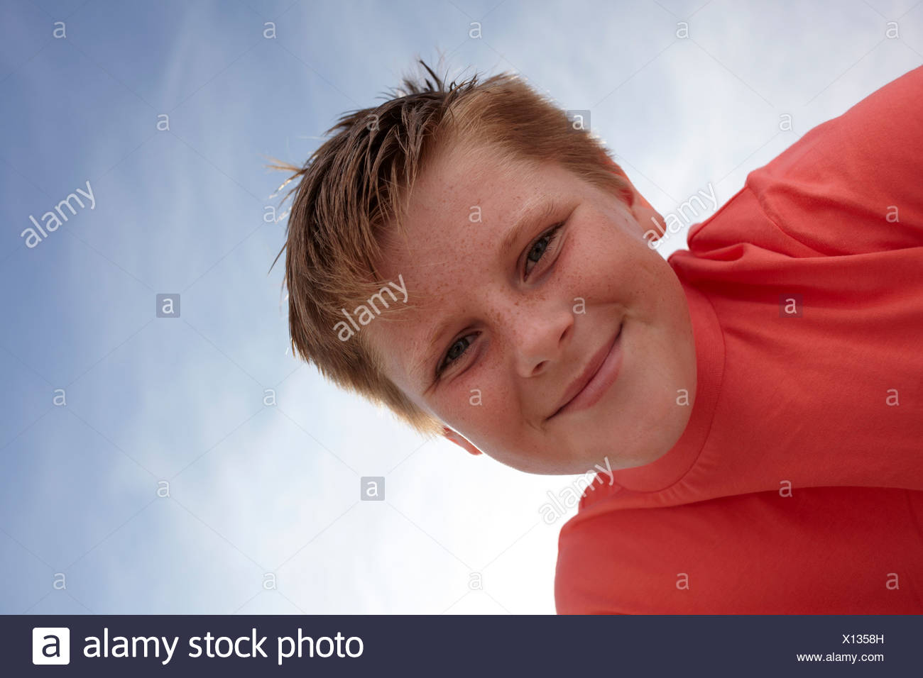 Boy looking at camera, viewed from below - Stock Image