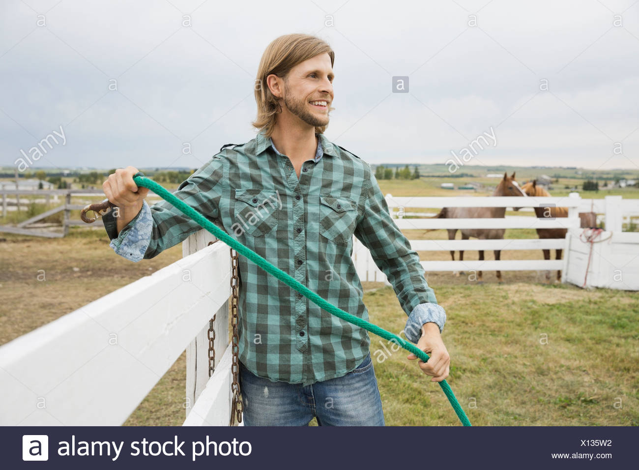 Man holding rope working on ranch - Stock Image