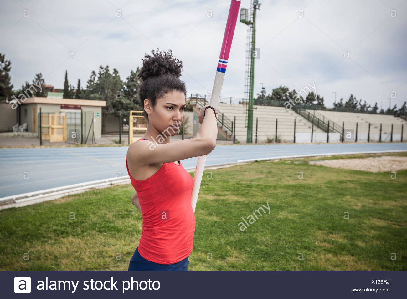 Young female pole vaulter concentrating at sport facility - Stock Image