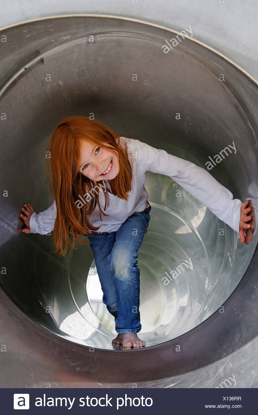 Girls playing in a tubular slippery dip at a playground Stock Photo