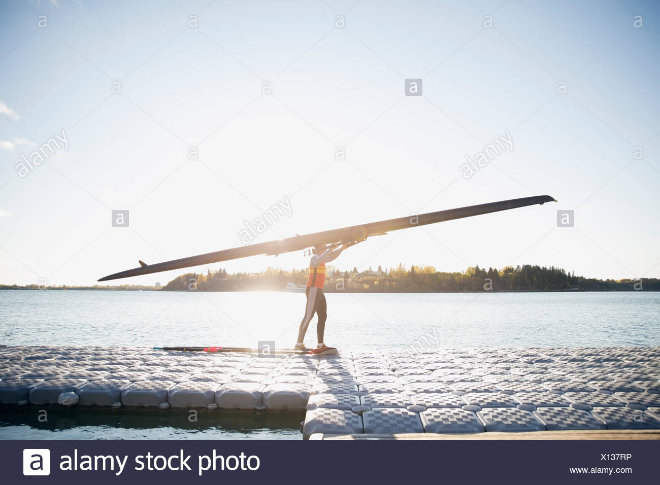 Rower carrying scull overhead at waterfront - Stock Image