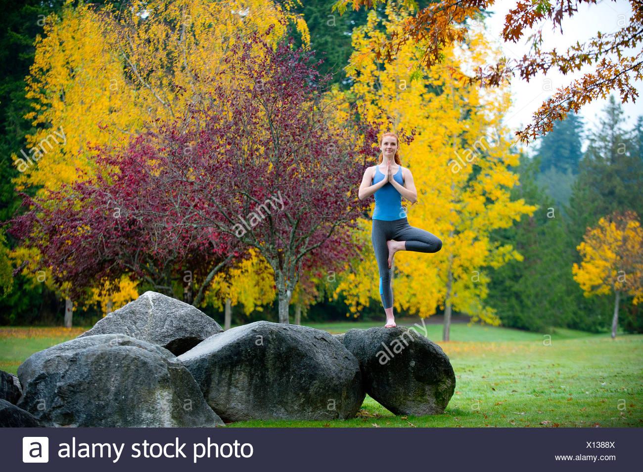 Young woman practising yoga on rock - Stock Image