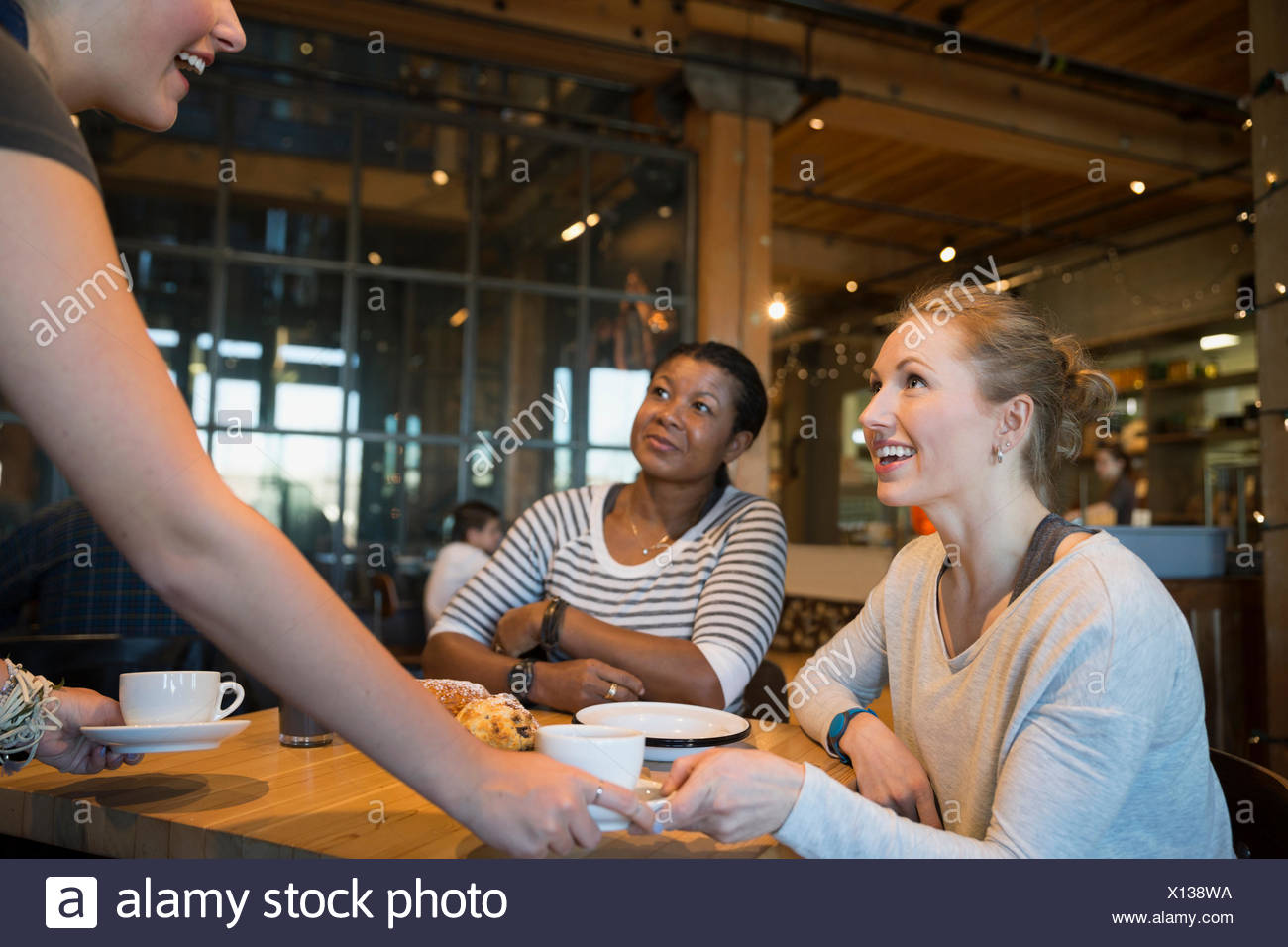 Bakery worker serving coffee to customers - Stock Image