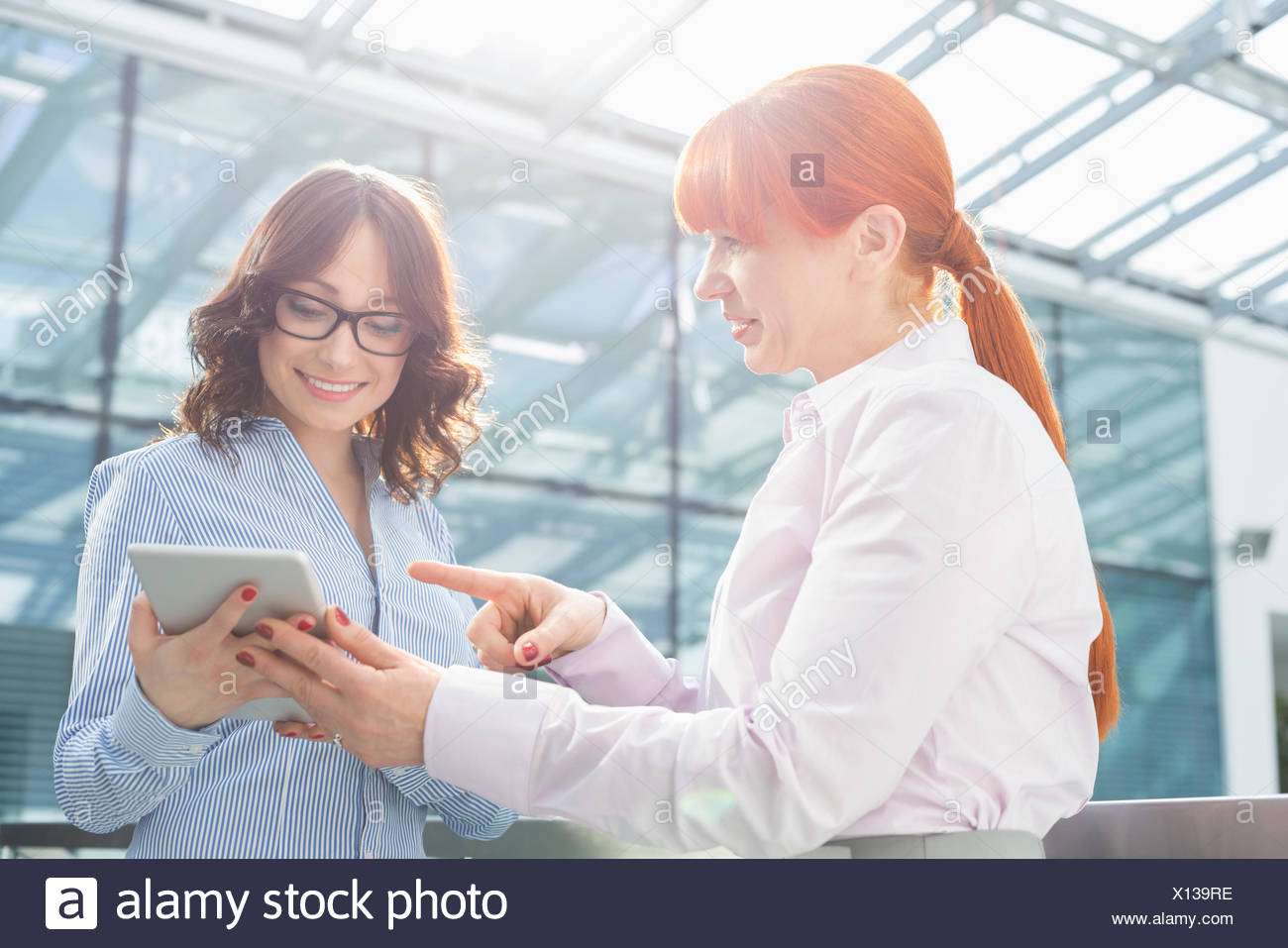 Businesswoman showing something on tablet PC to colleague in office - Stock Image