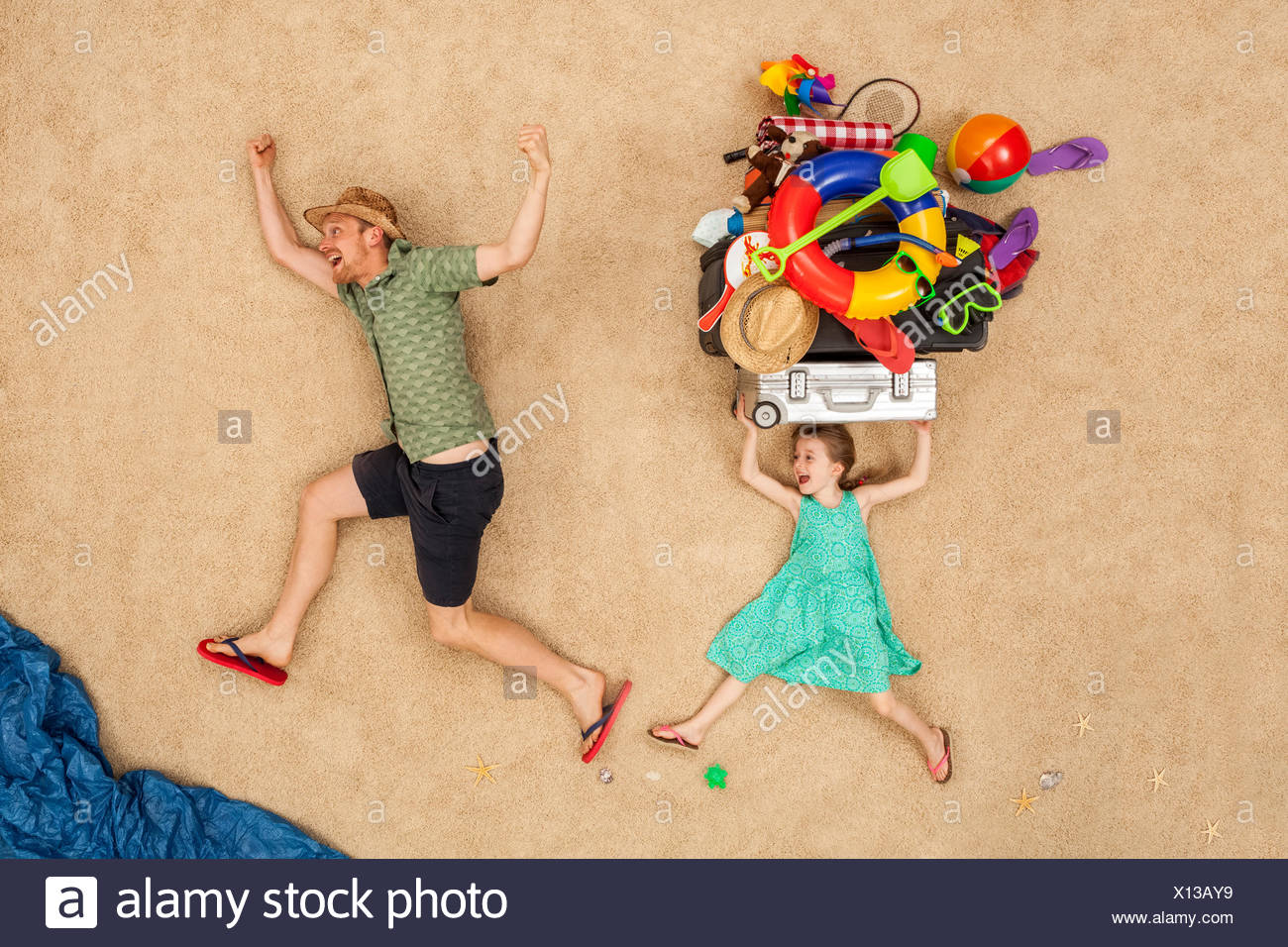 Father and daughter running to the sea, carrying beach equipment on the head - Stock Image
