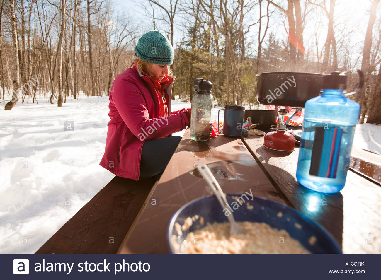 A woman eats breakfast while camping off the Kangamangus Highway near Conway, New Hampshire. - Stock Image