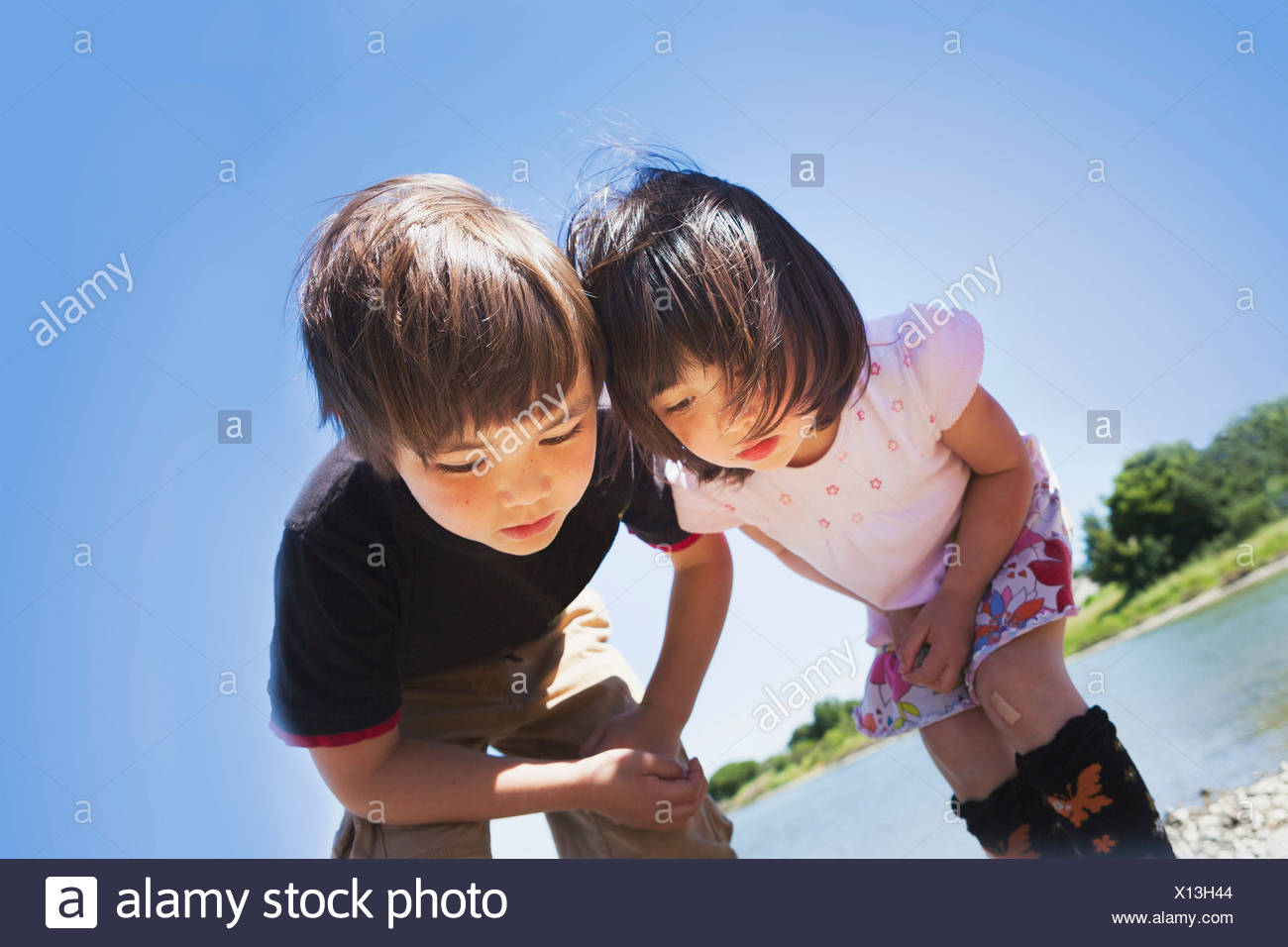 Boy and girl looking down at something Stock Photo