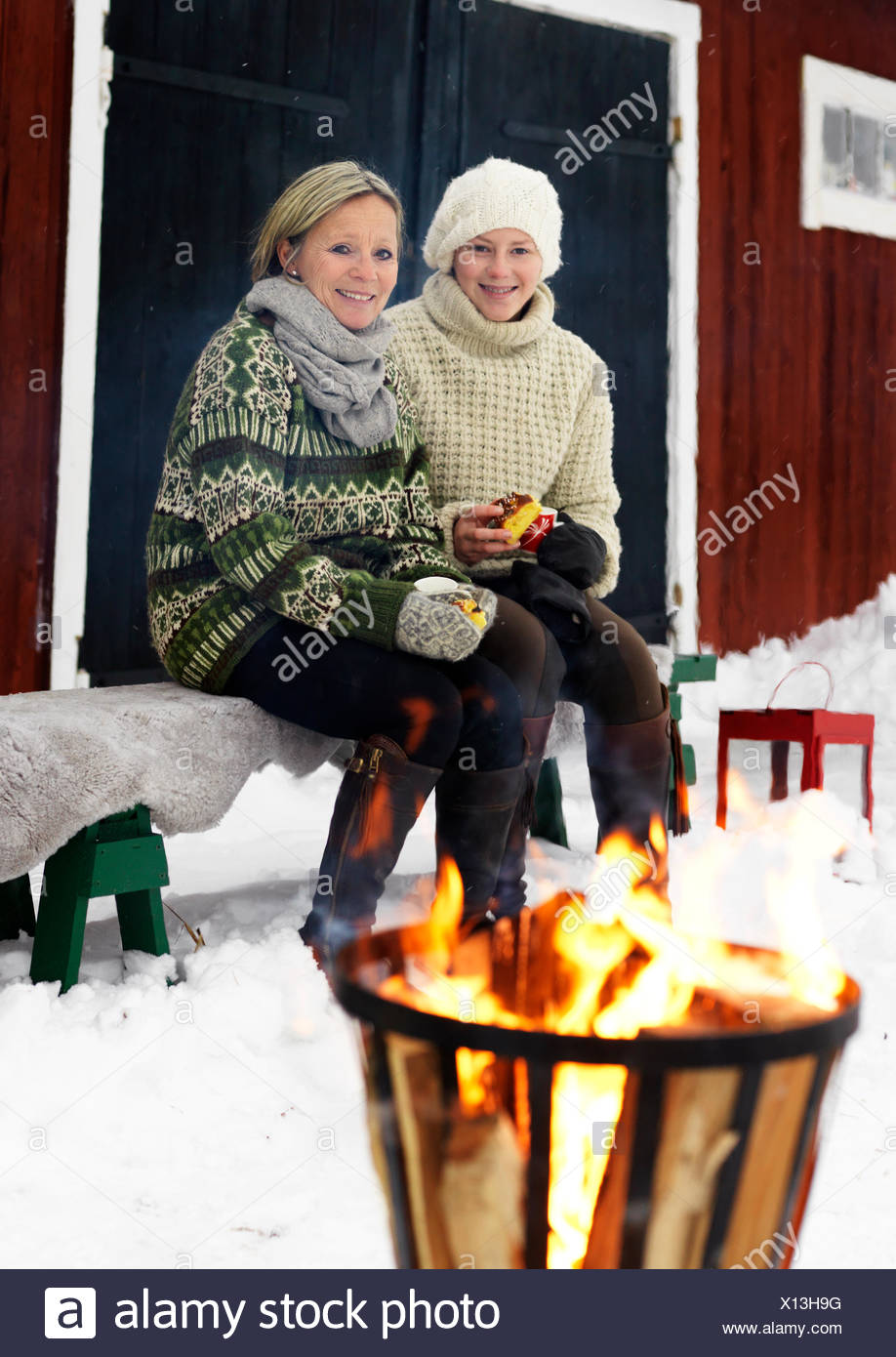 Sweden, Portrait of mother sitting with teenage girl (14-15) on bench in winter - Stock Image