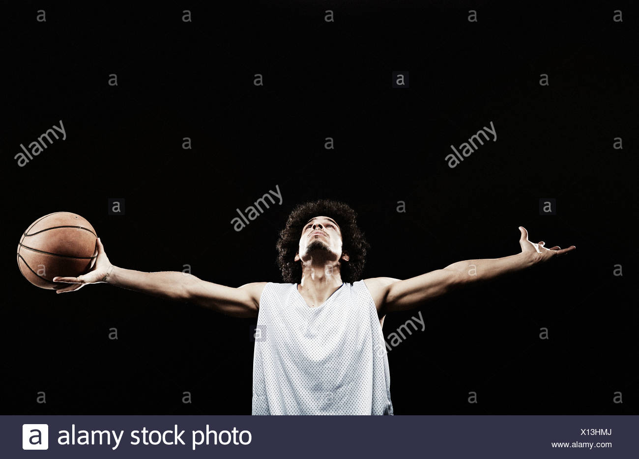 Basketball player holding basketball with arms out - Stock Image