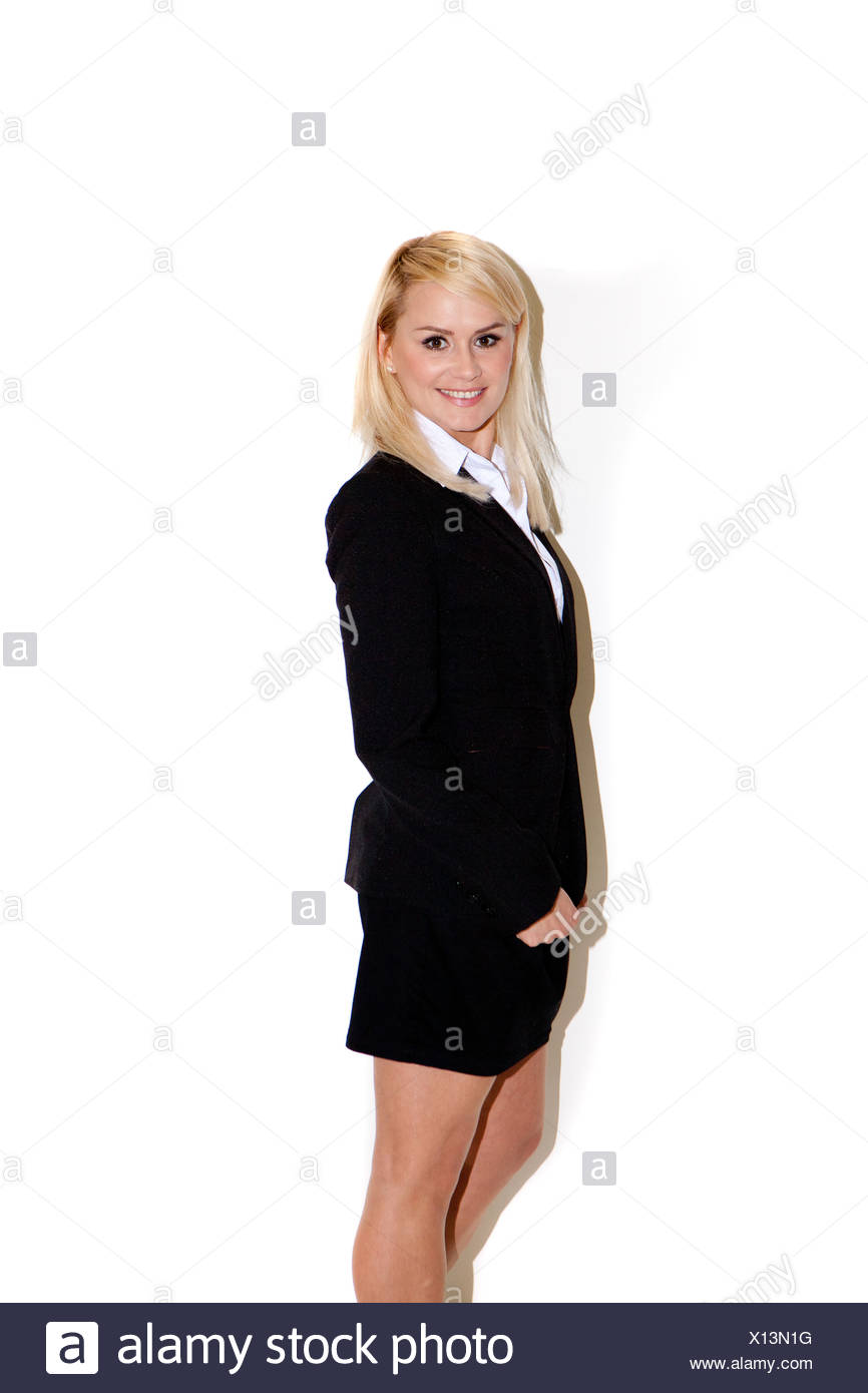 Smiling friendly businesswoman standing sideways in a stylish modern suit with a short miniskirt - Stock Image