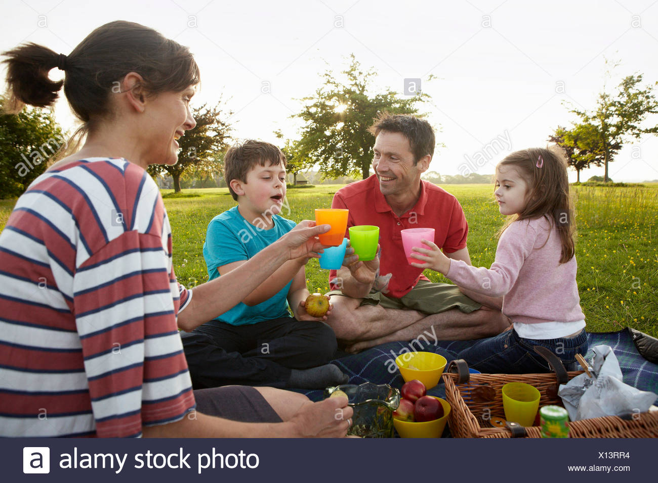 A family, two parents and two children outdoors in the summer having a picnic. - Stock Image