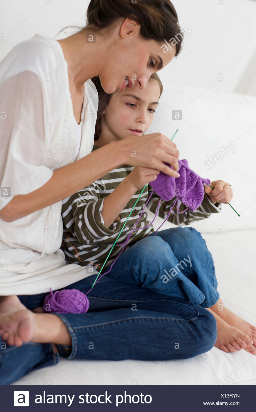 little girl shown how to knit - Stock Image