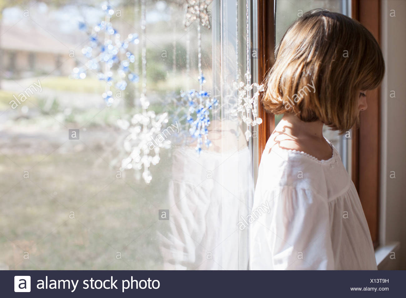 Side view of child beside dangling christmas ornaments - Stock Image
