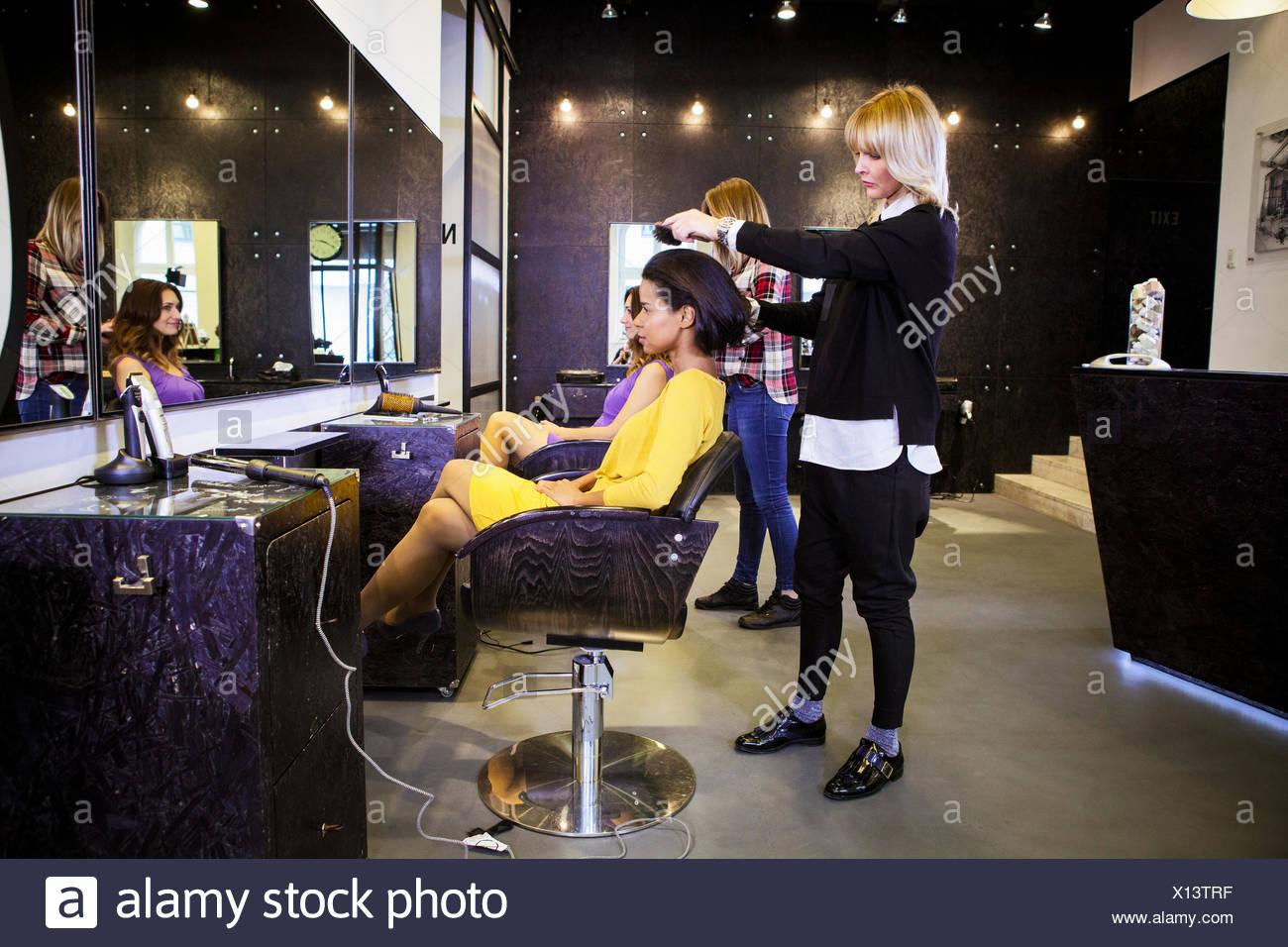 Hairdresser brushing customer's hair in hair salon - Stock Image