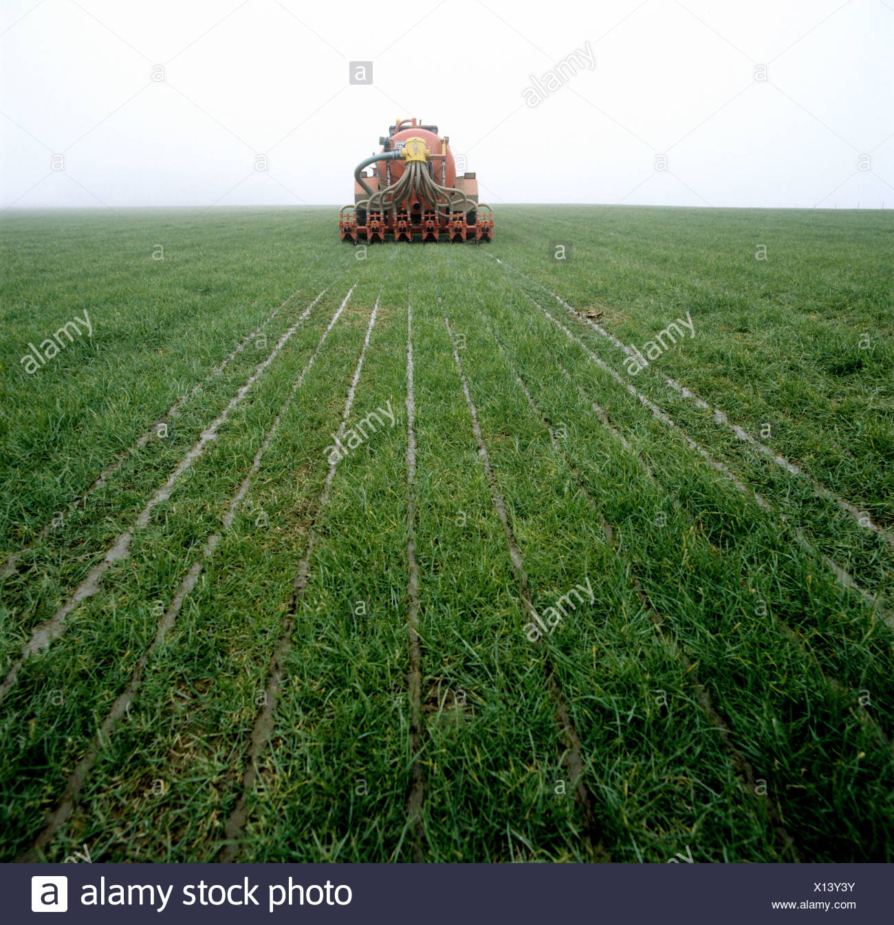 Tractor and Hispec slurry injector injecting slurry into grassland - Stock Image