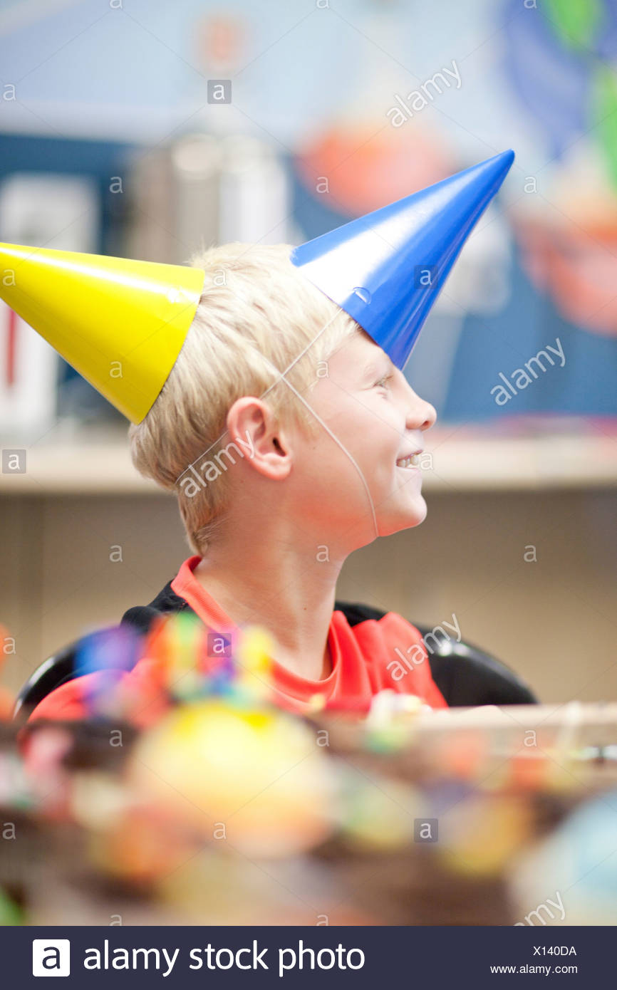 Boy at birthday party wearing two party hats Stock Photo