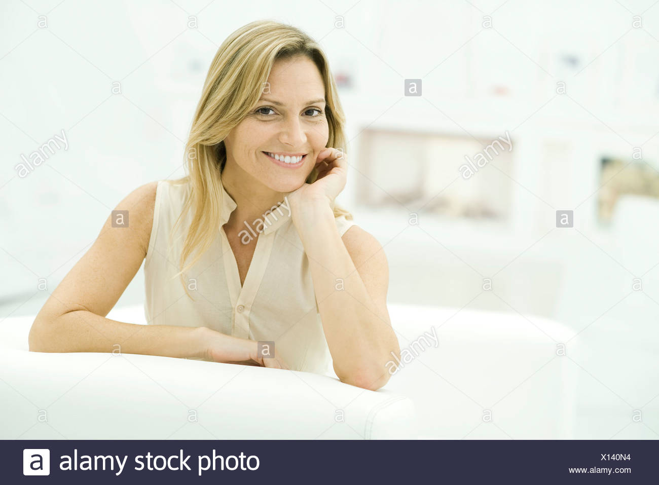 Woman leaning on elbow, smiling at camera, portrait - Stock Image
