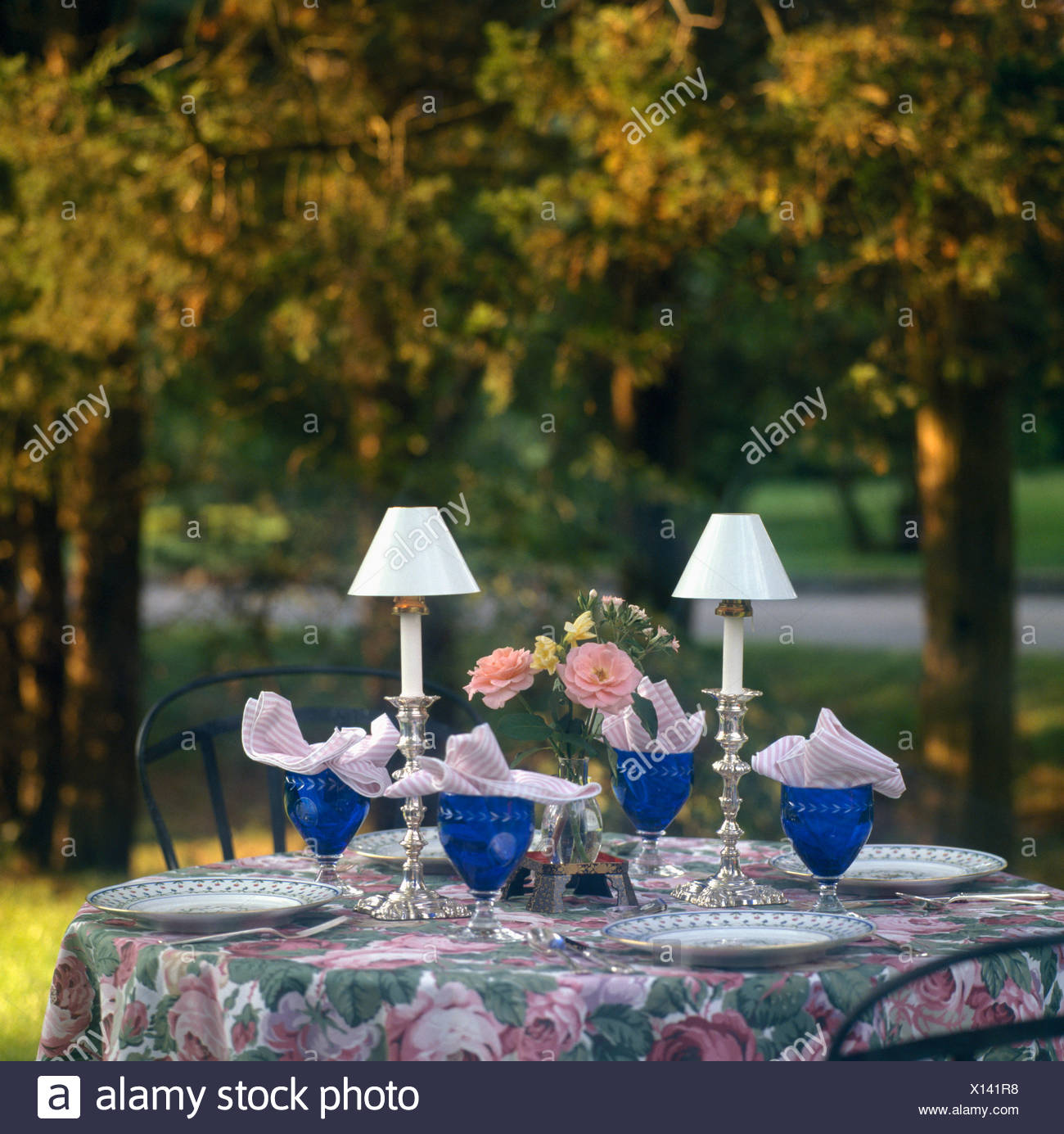 Close up of candle lamps and blue wine glasses on circular garden close up of candle lamps and blue wine glasses on circular garden table with rose patterned in early evening aloadofball Images