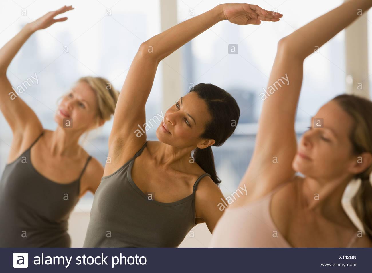 Multi-ethnic women practicing yoga - Stock Image