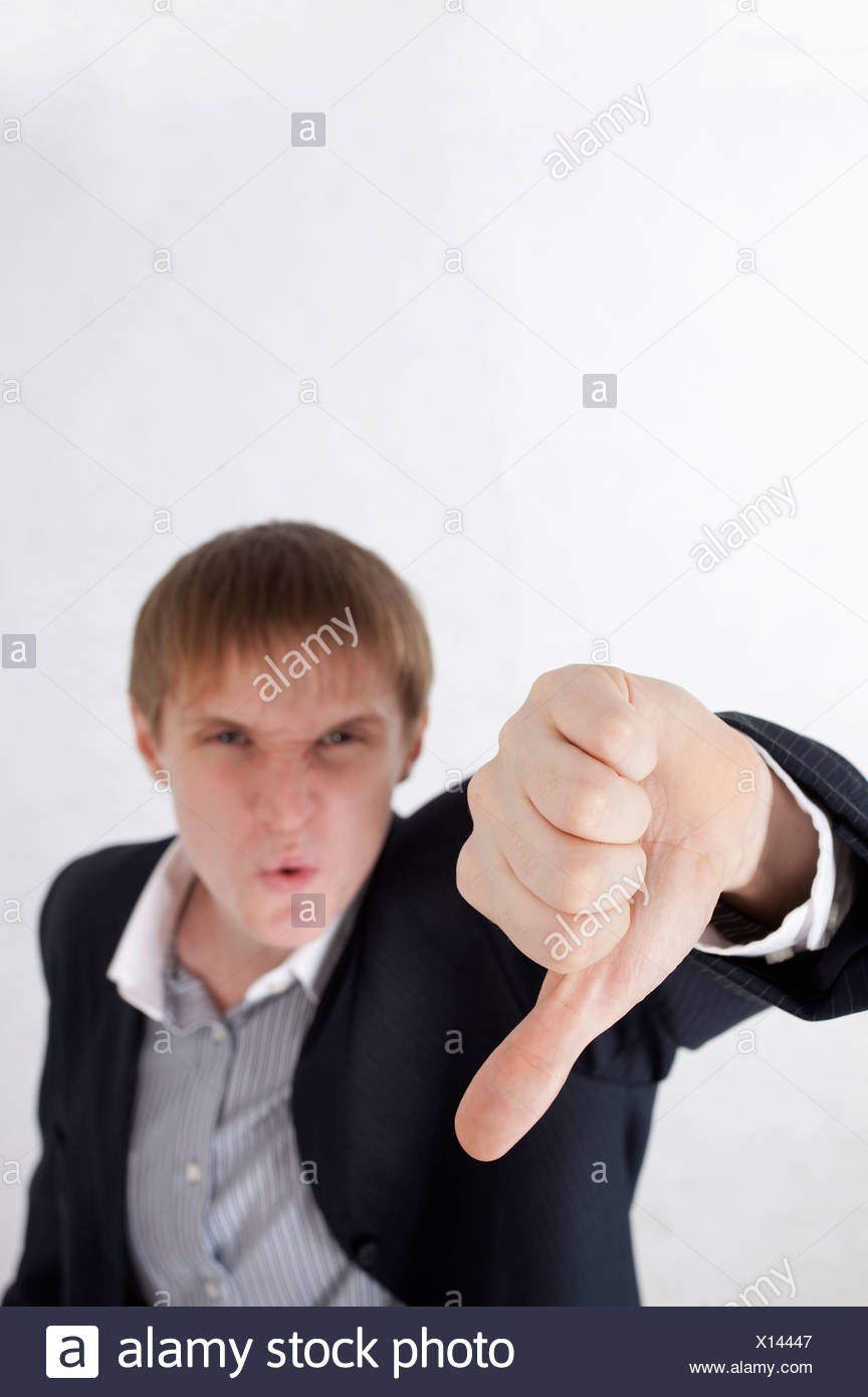 Young man frowning and making thumbs down - Stock Image
