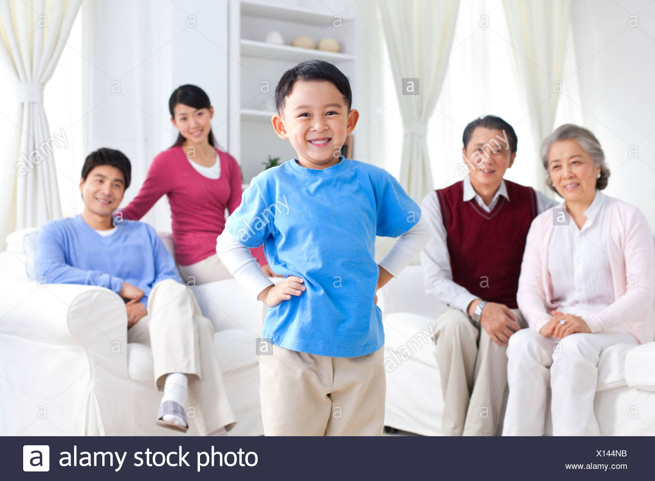Young Chinese boy with hands on hips, parents and grandparents behind him - Stock Image