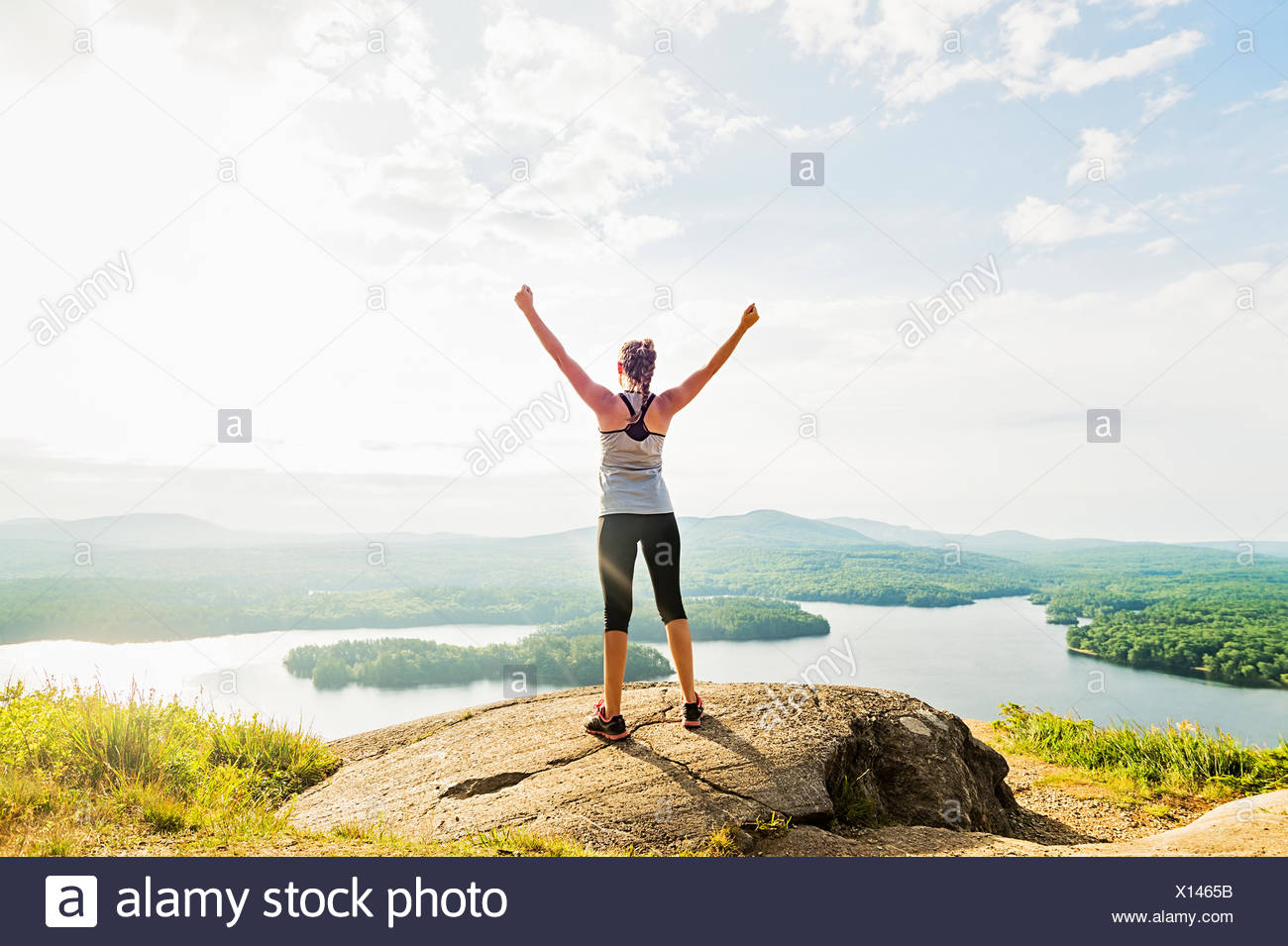 Young woman standing on top of mountain with outstretched arms, rear view - Stock Image
