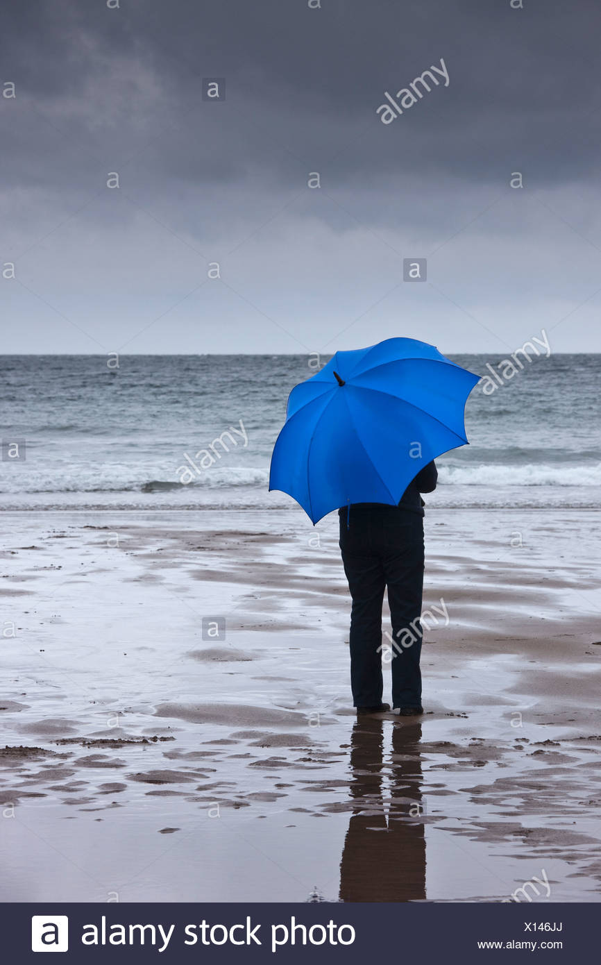 A Person Holding A Blue Umbrella Standing On The Beach Under A Dark Sky Northumberland England Stock Photo Alamy