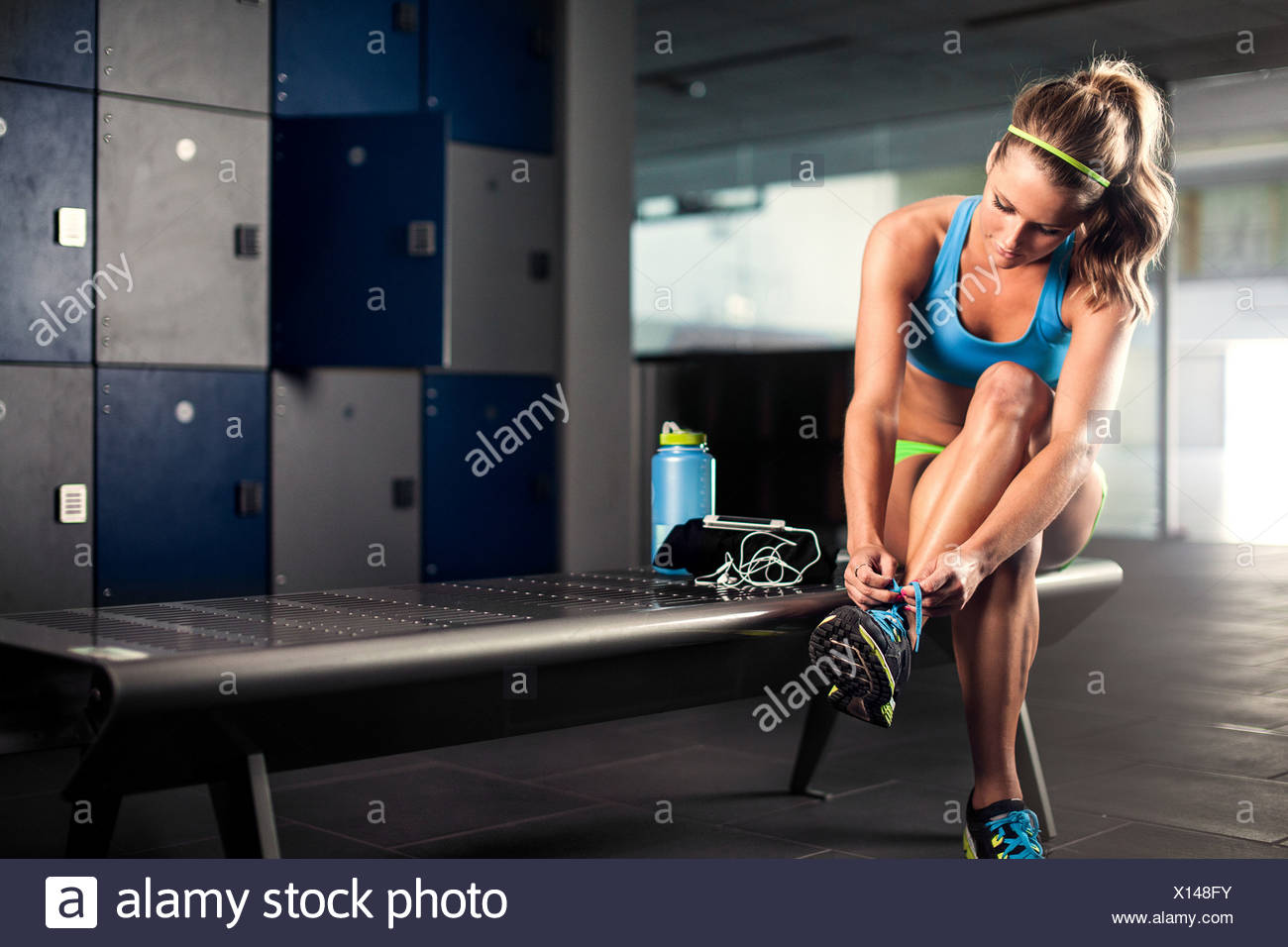 Young woman tying trainer lace in gym - Stock Image