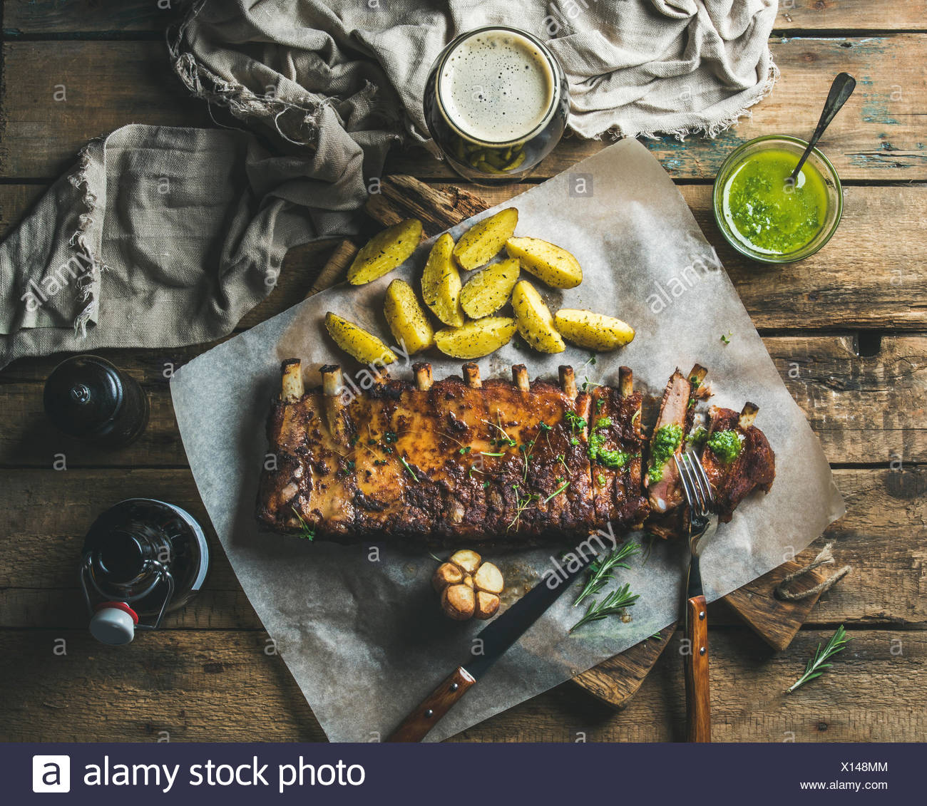 Roasted pork ribs partly cut into pieces with garlic, rosemary, green herb sauce, fried potato and dark beer on rustic wooden ba - Stock Image