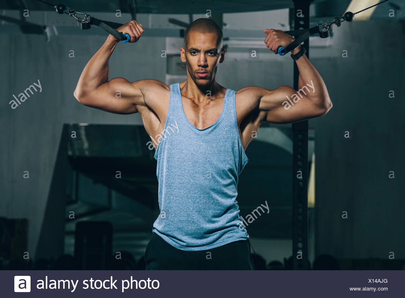 Young man training at cable crossover in gym - Stock Image