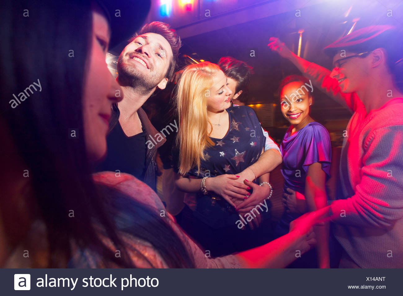 Group of people at party, man kissing woman's neck - Stock Image