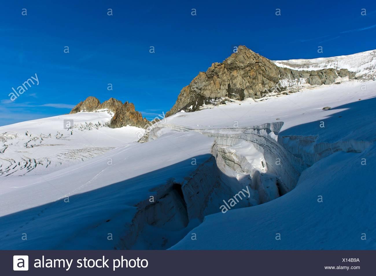 Crevasse on the glacier Plateau du Trient, peaks Tete Blanche and Aiguille du Tour behind, Valais, Switzerland. - Stock Image
